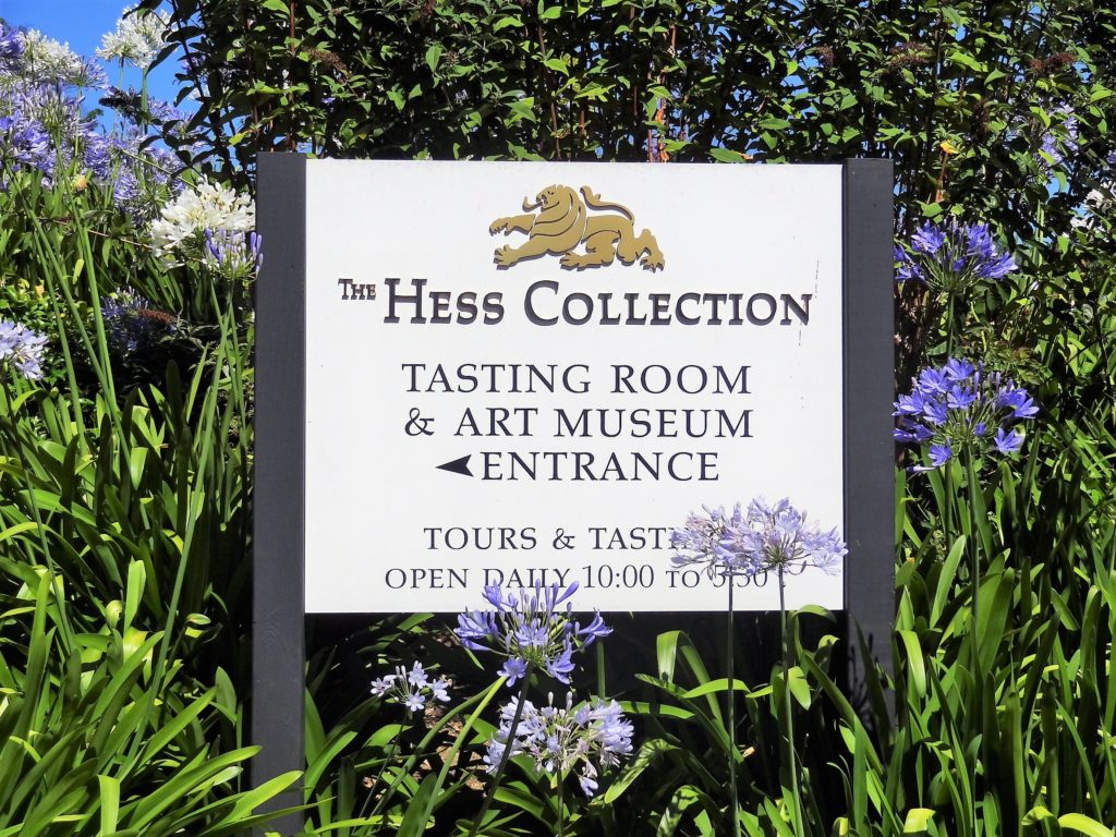 Hess Collection Sign at the entrance to the winery surrounded by blue and white Alliums