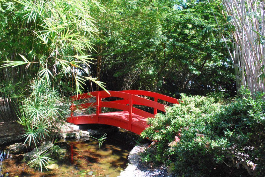 Red Japanese Bridge over a small stream in the Miami Beach Botanical Garden