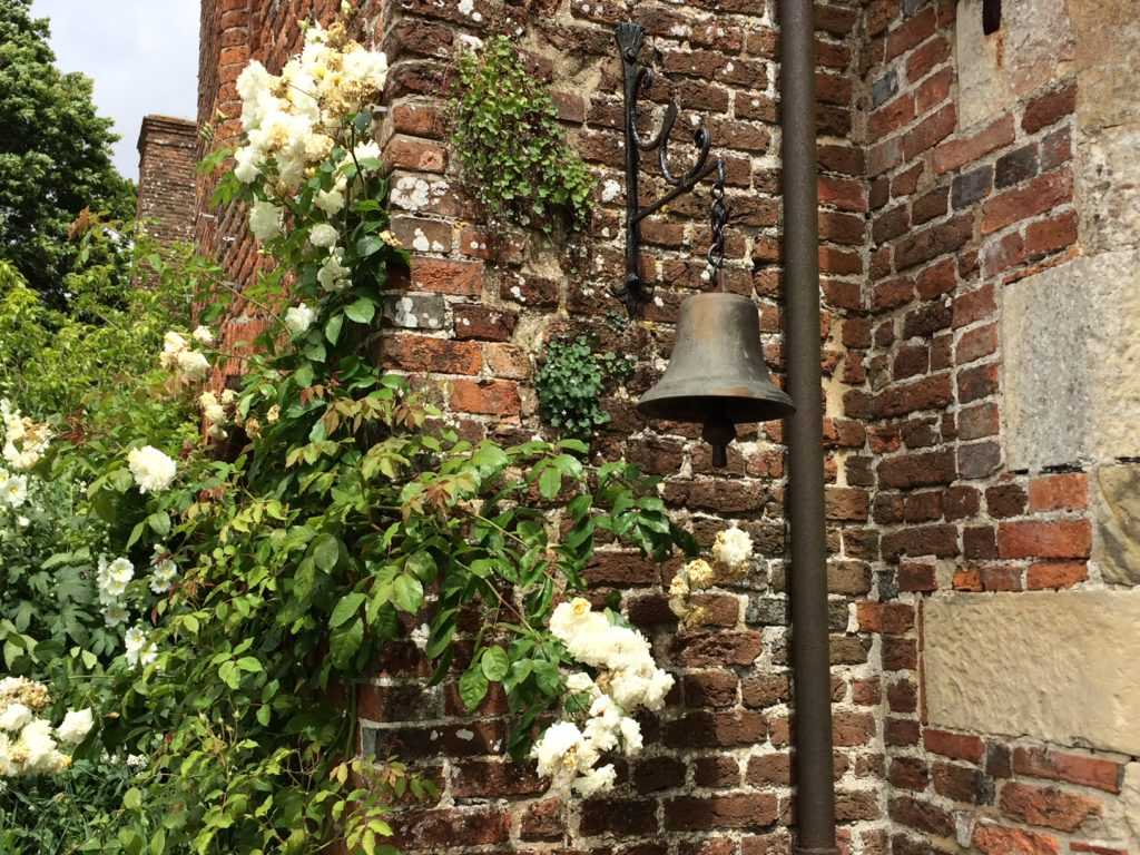 Bell with brickstone in background with a climbing white rose